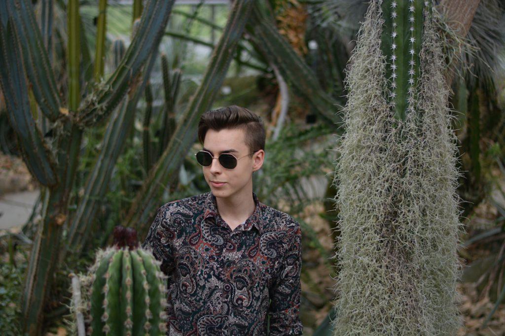 Blogger hat Fernweh. Steht zwischen Kakteen mit eckiger Sonnenbrille und Hemd in Paisley Muster