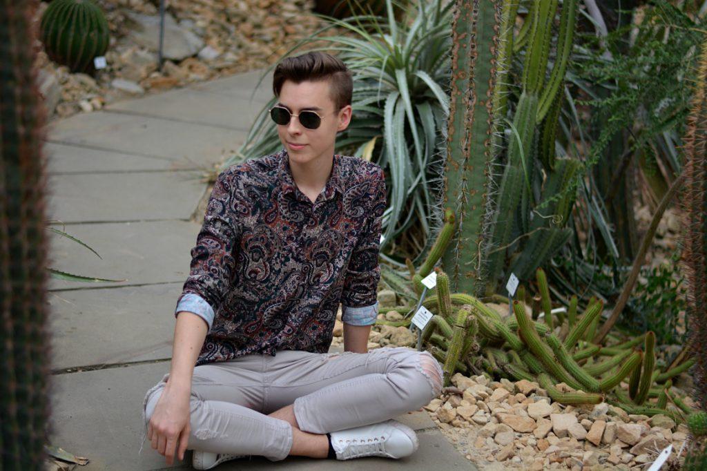 Blogger sitzt im Schneidersitz auf Gehweg im botanischen Garten Dresden. Um ihn exotische Pflanzen. Fernweh.