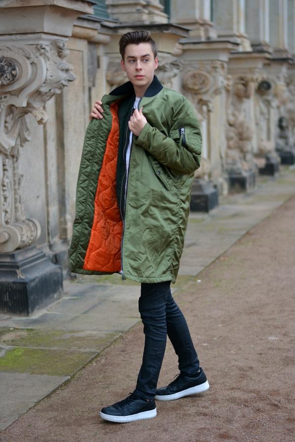 Modeblogger schaut zur Seite. Grüner Mantel mit schwarzer Hose und Schuhen