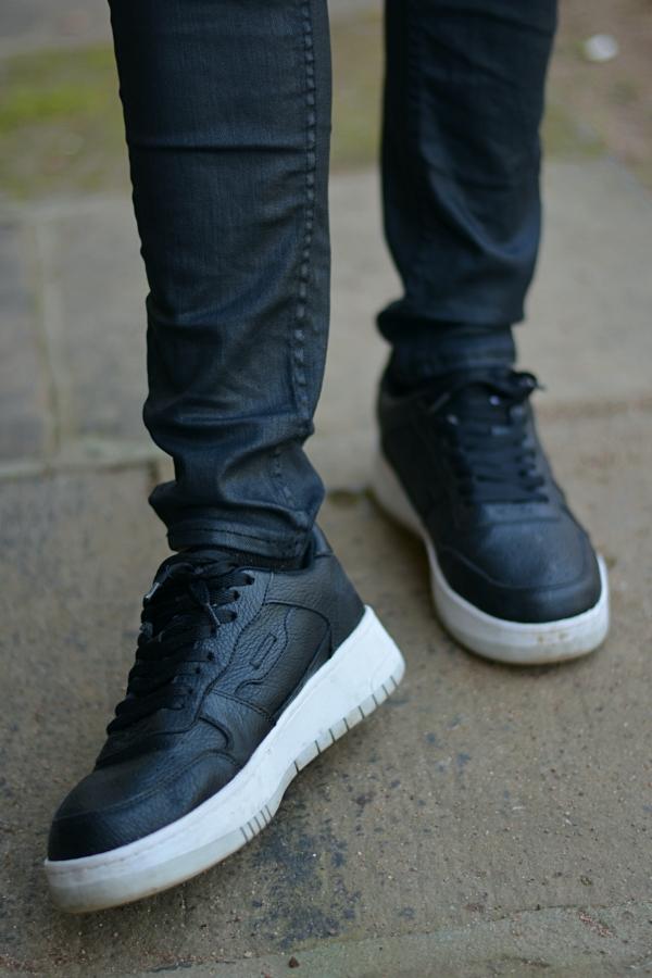 Detailaufnahme von schwarzen Schuhen und schwarzer Hose. Thema: Zeit.