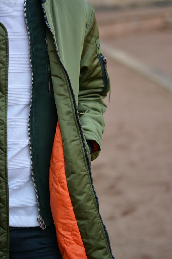 Detailbild grüner Mantel weißer Pullover.
