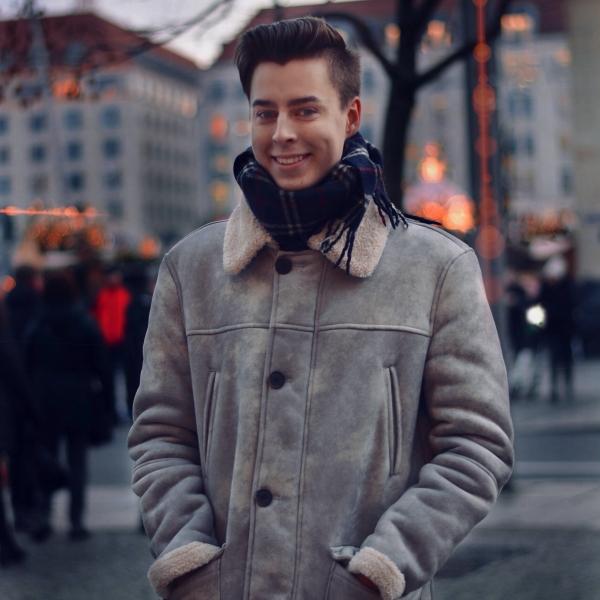 Pierre auf dem Weihnachtsmarkt mit grauer Jacke und blauem Schal
