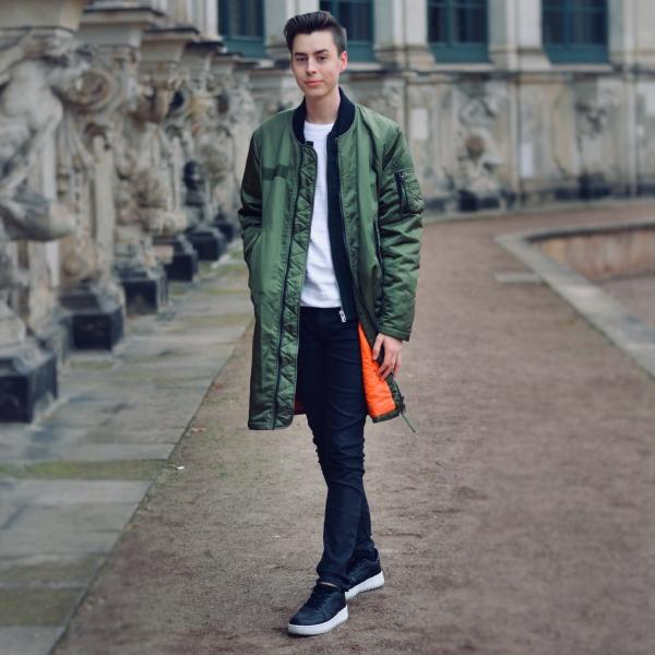 Modeblogger aus Dresden mit grünem langem Mantel, schwarzer Hose und schwarzen Schuhen