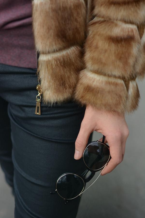 Detailbild von Outfit. Kunstpelzjacke und schwarze Hose.