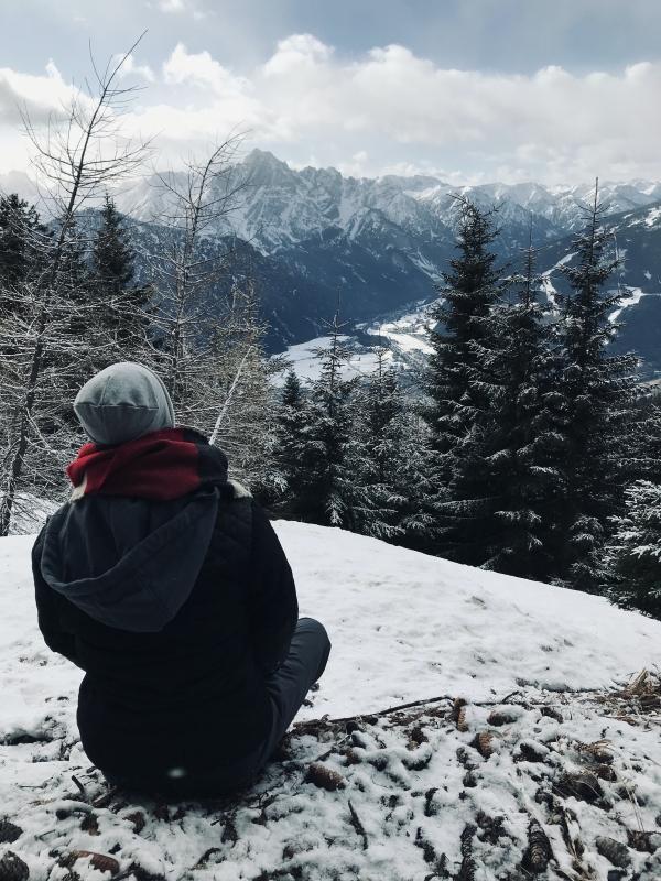 Blogger schaut in verschneites Tal in Österreich