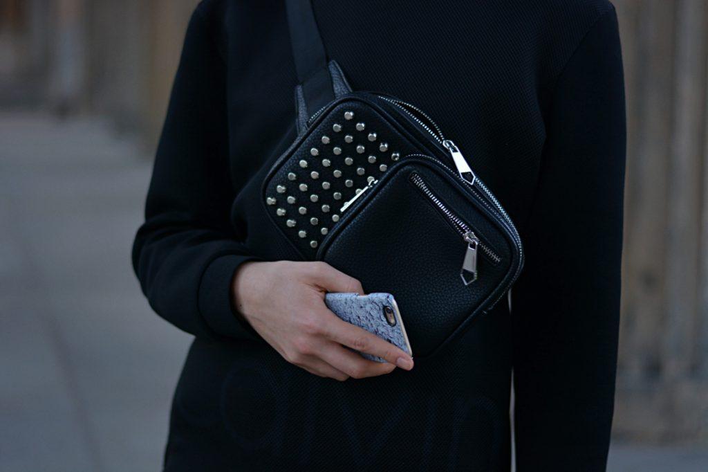 Detailaufnahme schwarze Gürteltasche mit Nieten und blaue Handyhülle