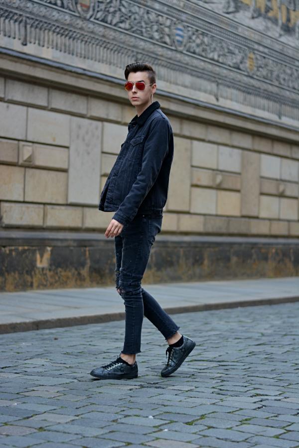Modeblogger vor Fürstenzug in Dresden Outfit in schwarz und Brille in orange - stylisch
