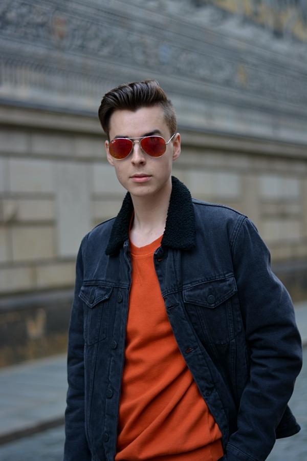 Modeblogger Pierre in schwarzer Jeansjacke und Pullover und Sonnenbrille in orange