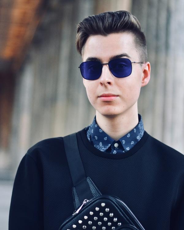 Blogger mit schwarz/blauem Outfit mit Sonnenbrille und Gürteltasche