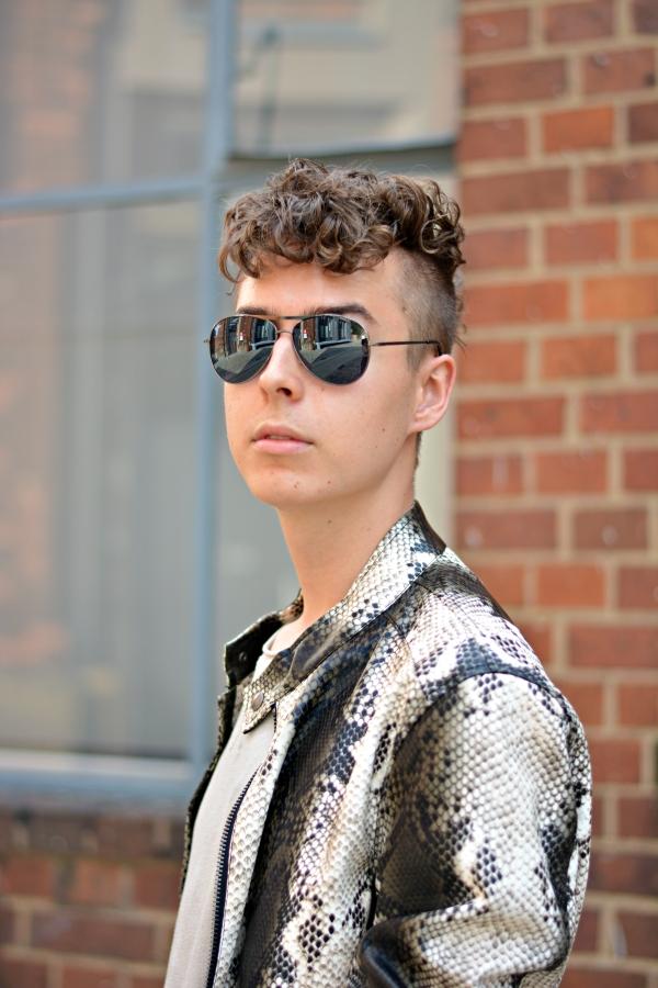 Portrait von jungem Mann in Animal Print Lederjacke und Locken