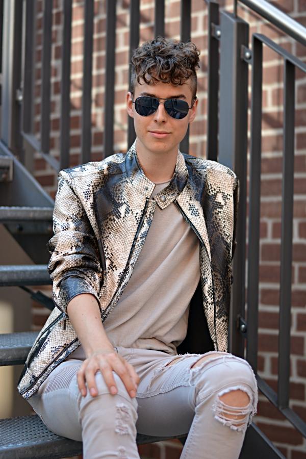 Junger Mann mit Locken und Animal Print Lederjacke auf einer Metalltreppe sitzend