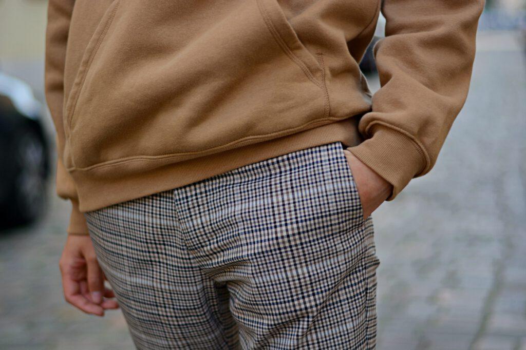 Detailaufnahme von braunem Pulli und karierte Stoffhose