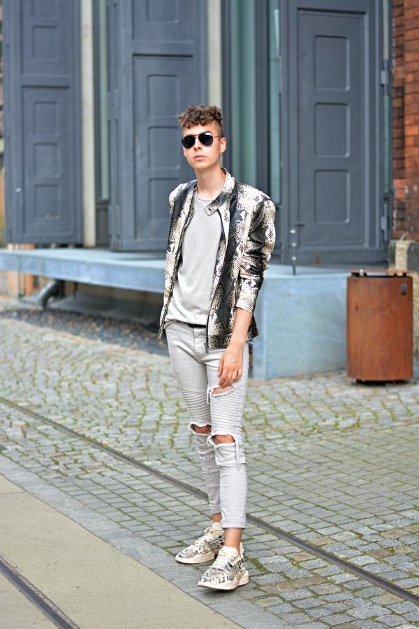 Junger Mann in Outfit in beige und Schlangenoptik