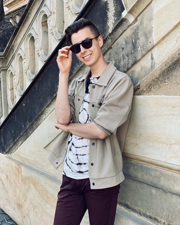 Beige Wand davor Modeblogger in beige, weiß,rot und Sonnenbrille