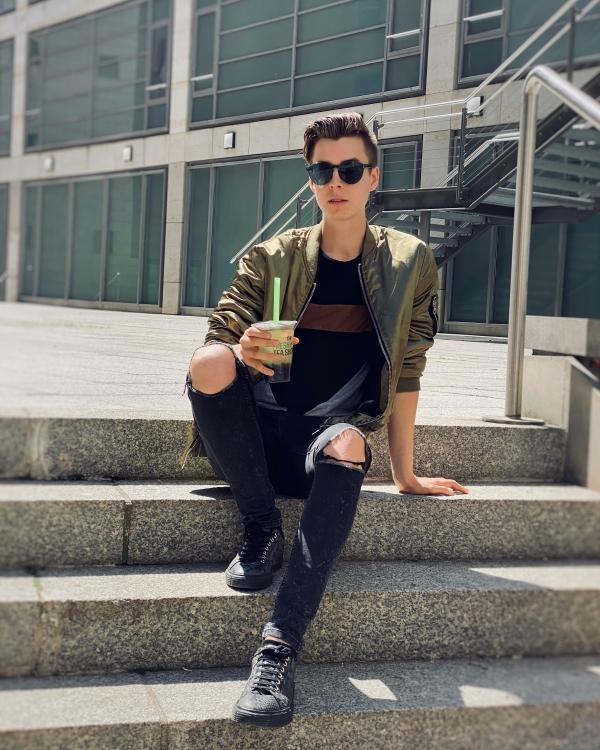 Junger Mann sitzt auf Treppe mit Bubble Tea in der Hand