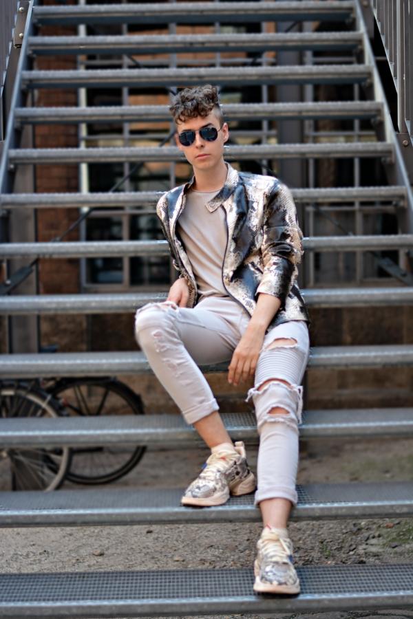 Junger Mann in Animal Print Lederjacke sitzend auf einer Metalltreppe