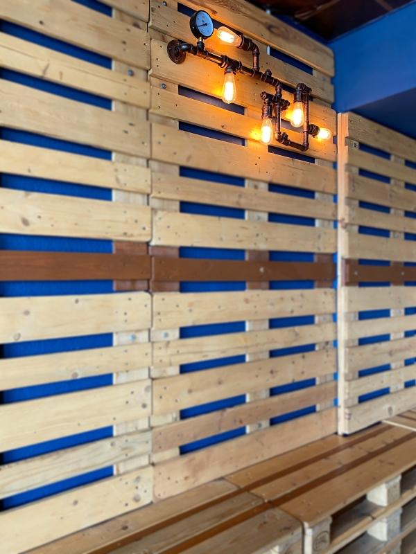 Holzpaletten an der Wand. In der oberen rechten Ecke eine Lampe