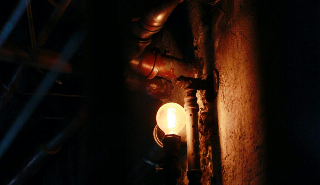Escape Room in Berlin. Leuchte mit Rohren in dunklem Raum.