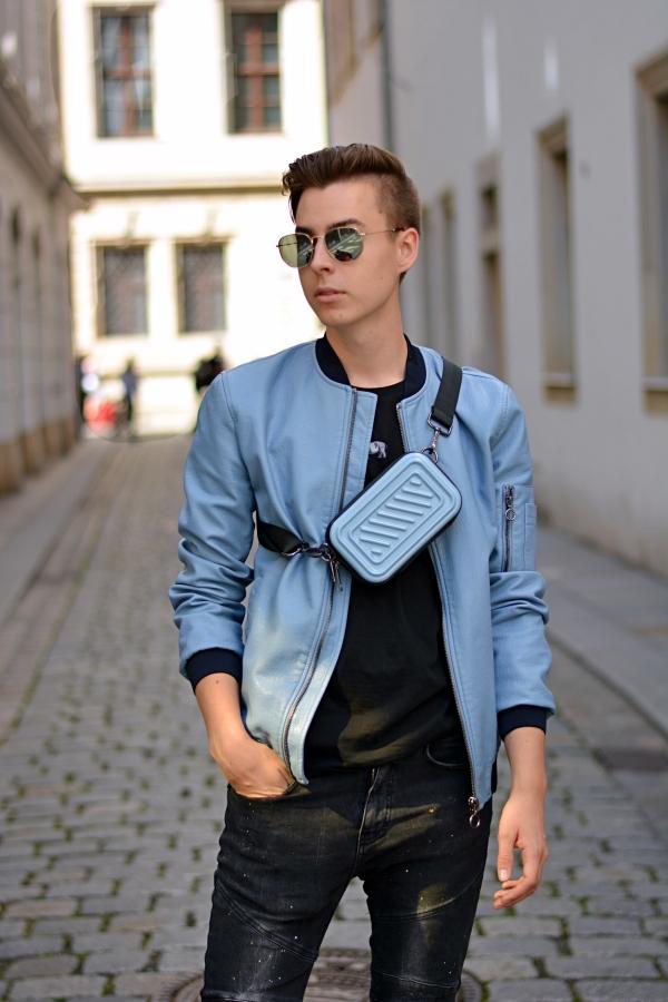 portraitfoto von jungen Mann in blauer Jacke und Umhängetasche