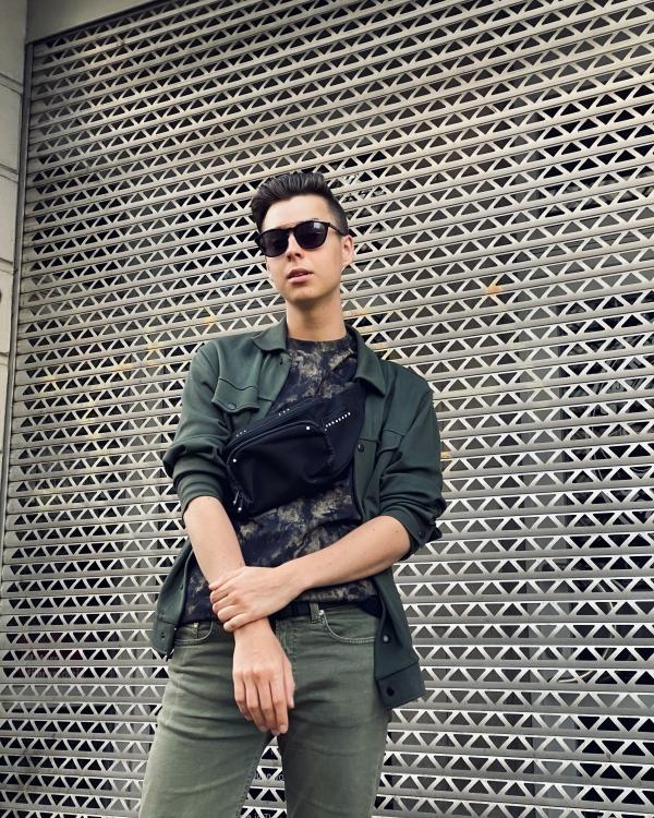 Modeblogger in grünem Outfit mit Sonnenbrille