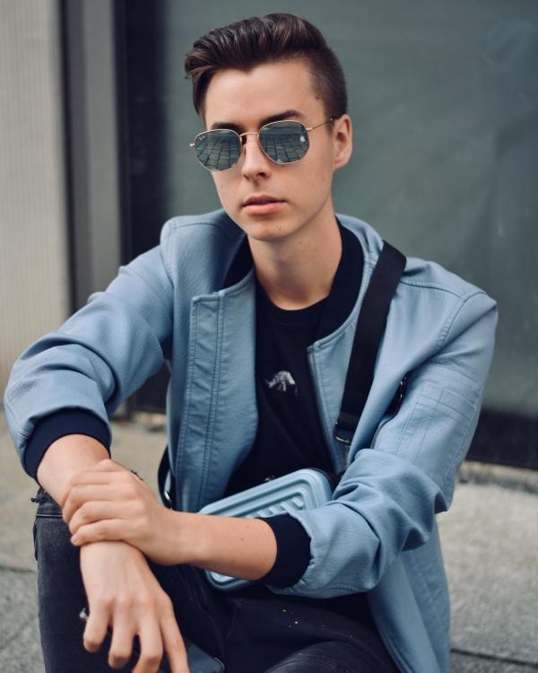Junger Mann sitzt auf Boden in stylischem Outfit in hellblau. Aufgenommen im Oktober