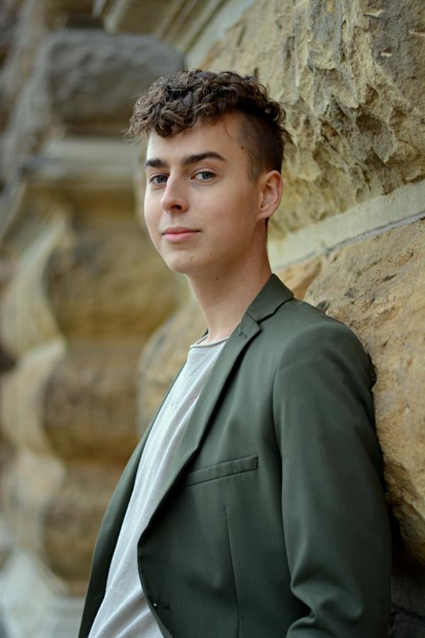 Portraitaufnahme junger Mann mit Locken und in Anzug.