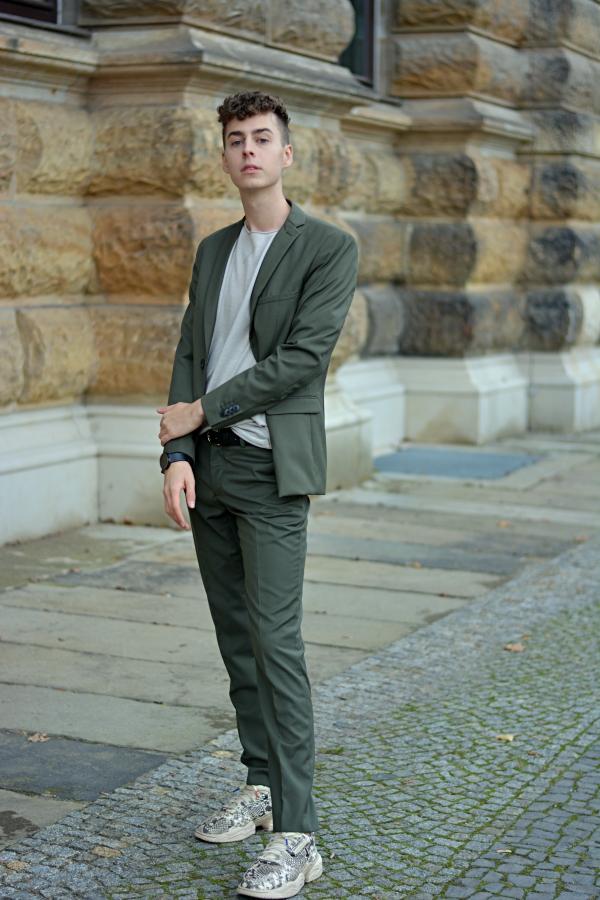 Junger Mann trägt grünen Anzug mit hellgrauem T-Shirt