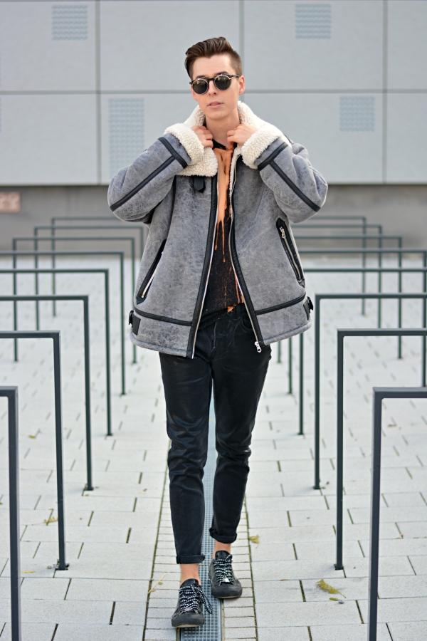 Outfit von jungem Mann in schwarzer Hose und grauer Jacke