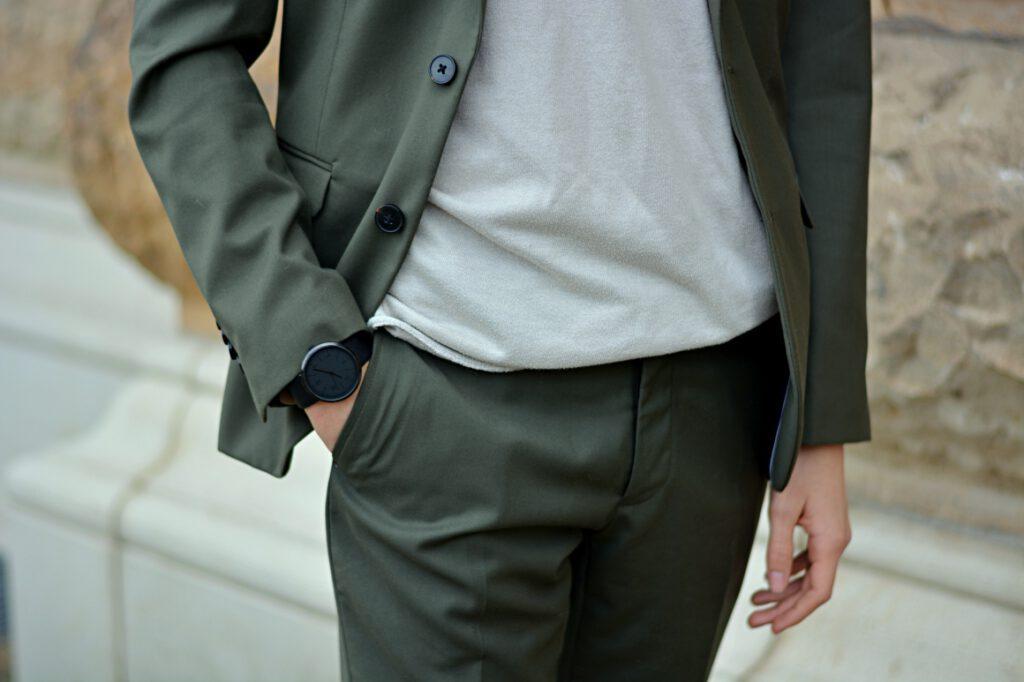 Detail von grünem Anzug. Anzug im Alltag mit T-Shirt und Sneaker.