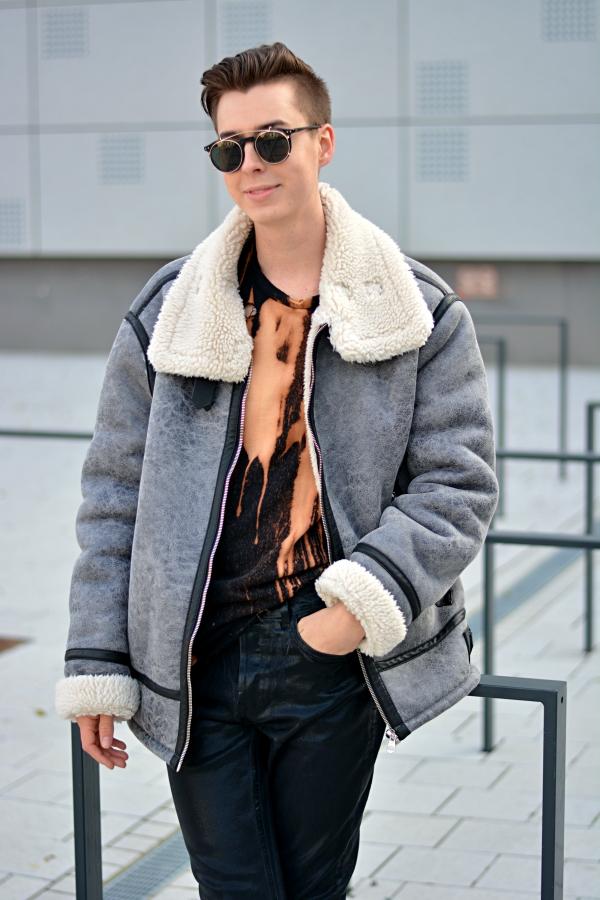 Selbstbewusstsein ausstrahlen kann schwierig sein, aber Mode kann dabei helfen. Junger Mann lächelt in grauer, oversize Jacke.