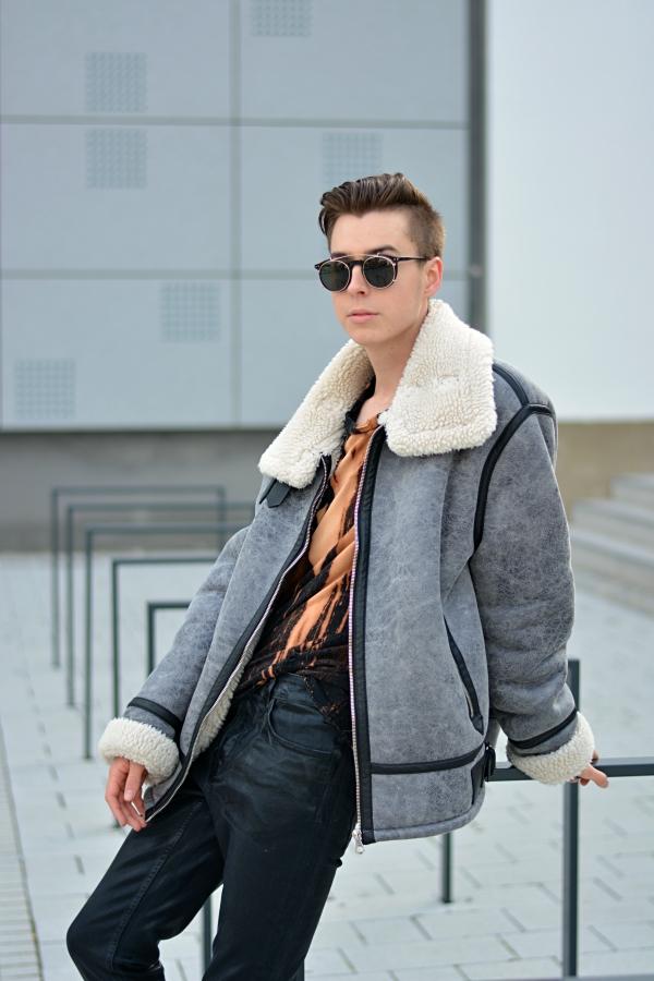Modeblogger lehnt an Fahrradständer in oversize Jacke