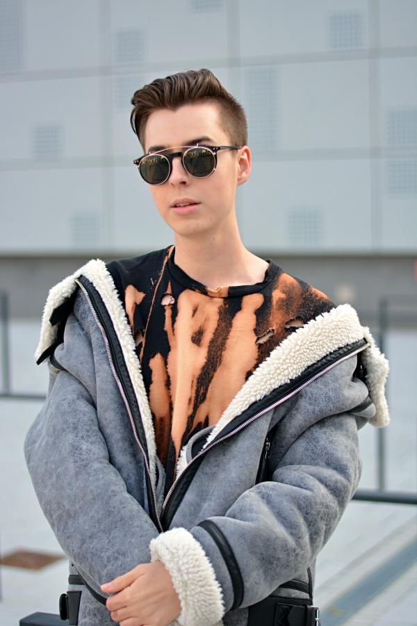 Portrait das Selbstbewusstsein ausstrahlt. Schwarze Sonnenbrille, graue Jacke, Pulli in Batikoptik.