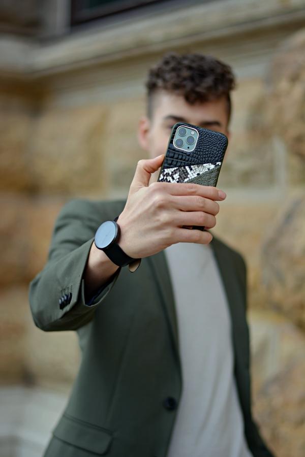 Junger Mann macht Selfie. Handyhülle in Fokus mit geprägtem Kunstleder