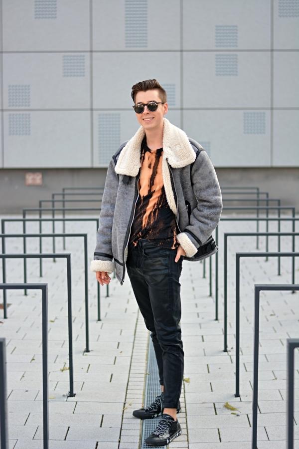 Modeblogger vor grauem Hintergrund in Outfit in schwarz, orange/beige und grau