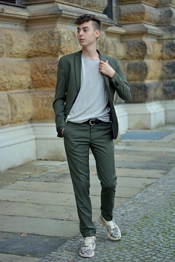 Anzug im Alltag. Junger Mann vor Sandsteinwand. Anzug in grün.