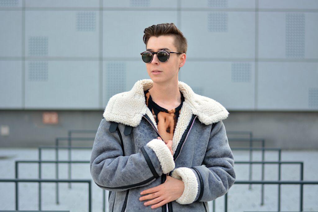 Portrait, grauer Hintergrund, graue, oversize Jacke, schwarze Sonnenbrille.