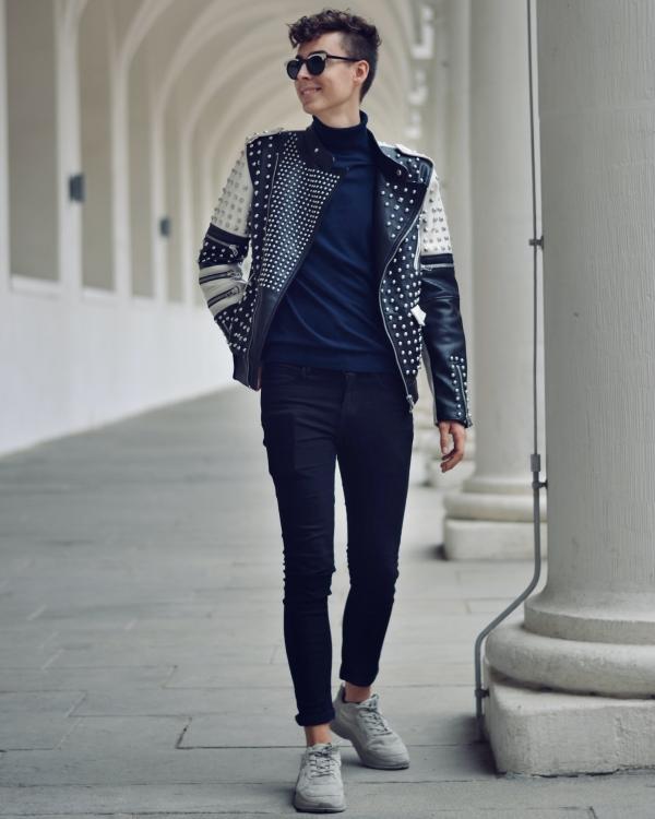Junger Mann mit Locken und Lederjacke mit Nieten vor weißem Hintergrund