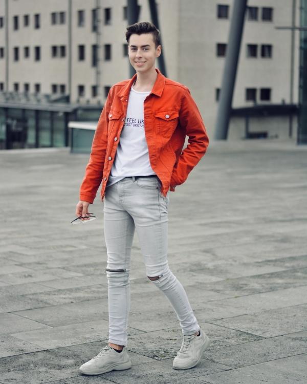 Junger Mann mit grauer Hose und Jacke in orange. Follower ohne Ende