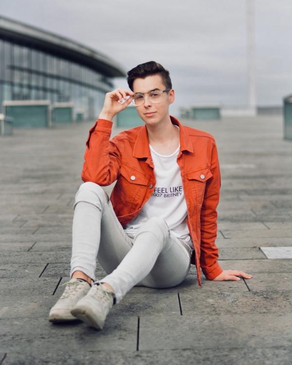 Modeblogger muss Bewerbungen schreiben. Sitzt auf Boden mit Brille