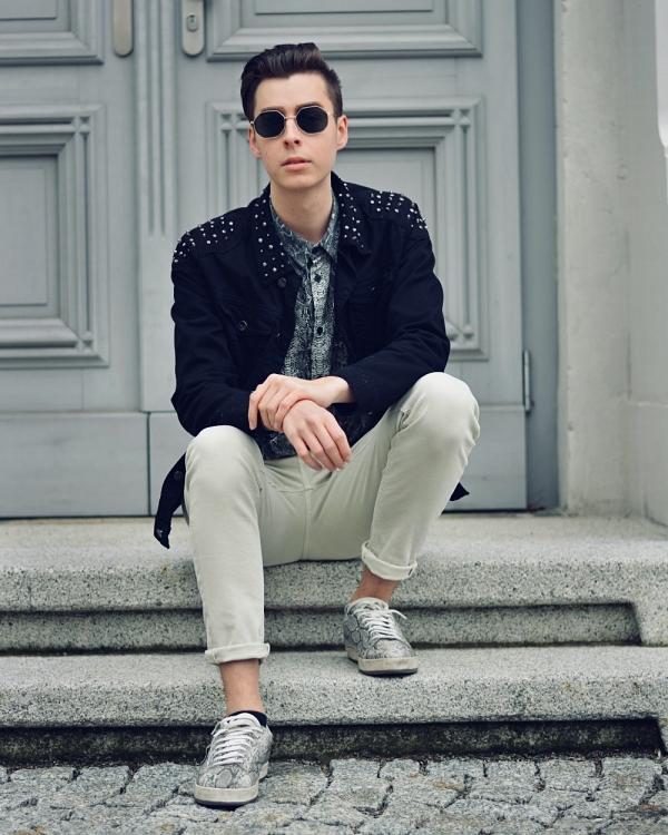 Junger Mann sitzt auf Treppe mit Sonnenbrille. Bewerbung