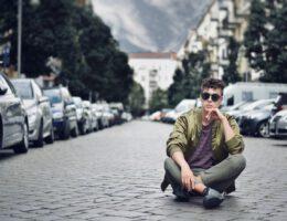 Typ sitzt auf einer Straße umringt von parkenden Autos
